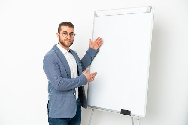 화이트 보드에 프레젠테이션을 흰색 배경에 고립 된 젊은 잘 생긴 백인 남자