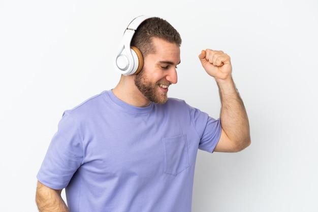 音楽を聴いて踊る白い背景で隔離の若いハンサムな白人男性