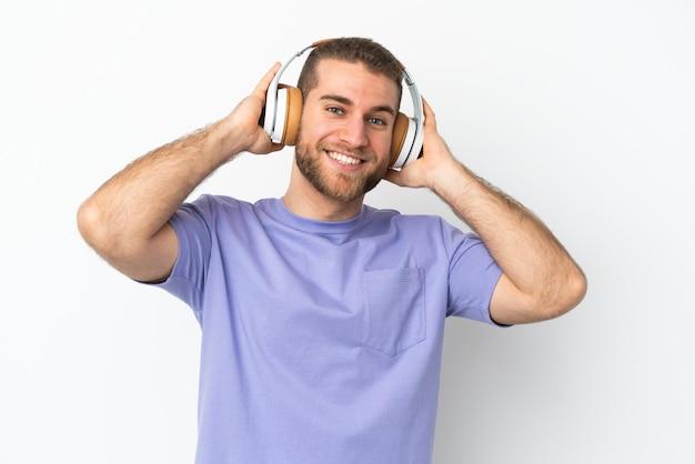 音楽を聴いて白い背景で隔離の若いハンサムな白人男性
