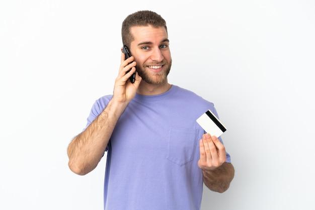 Молодой красивый кавказский мужчина изолирован на белом, разговаривает по мобильному телефону и держит кредитную карту