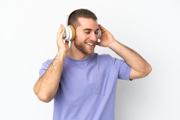 音楽を聴いて歌う白いで孤立した若いハンサムな白人男性