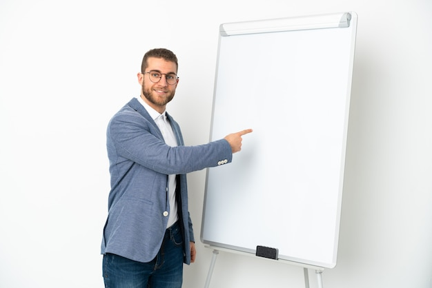 화이트 보드에 프레젠테이션을하고 그것에 쓰기 흰 벽에 고립 된 젊은 잘 생긴 백인 남자