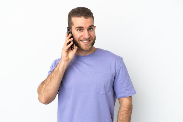 누군가와 휴대 전화로 대화를 유지하는 흰 벽에 고립 된 젊은 잘 생긴 백인 남자