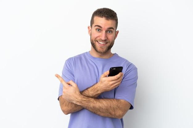 휴대 전화를 사용하고 다시 가리키는 흰 벽에 고립 된 젊은 잘 생긴 백인 남자