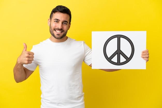 Молодой красивый кавказский мужчина изолирован на желтом фоне, держа плакат с символом мира с большим пальцем вверх