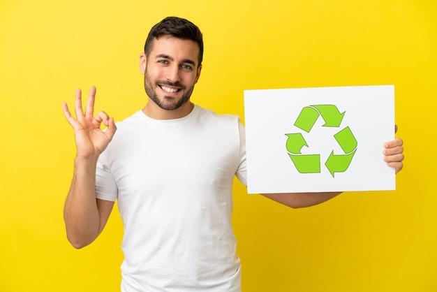 Молодой красивый кавказский мужчина изолирован на желтом фоне, держит плакат с иконой корзины и празднует победу