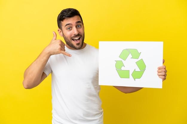 Молодой красивый кавказский мужчина изолирован на желтом фоне, держа плакат со значком корзины и делая жест телефона