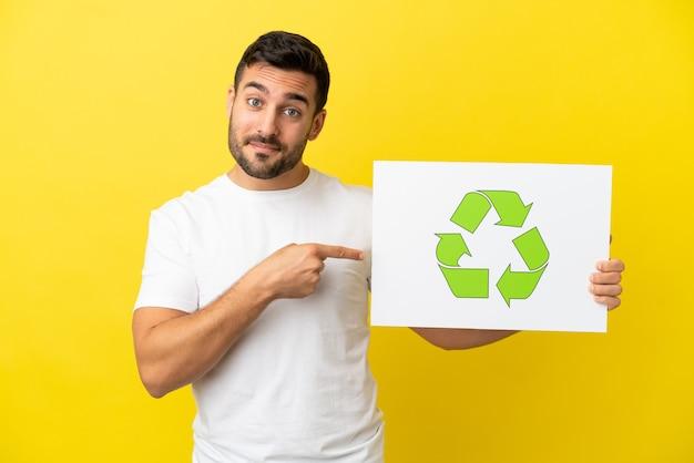 Молодой красивый кавказский мужчина изолирован на желтом фоне, держа плакат со значком корзины и указывая на него