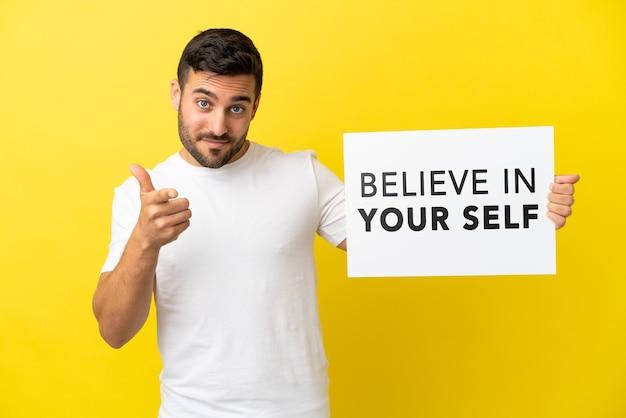 노란색 배경에 격리된 젊고 잘생긴 백인 남자는 자신을 믿으라는 문구가 적힌 플래카드를 들고 앞을 가리키는