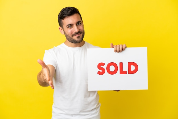 Молодой красивый кавказский мужчина изолирован на желтом фоне, держа плакат с текстом продано, заключая сделку