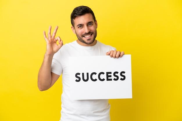 Молодой красивый кавказский мужчина изолирован на желтом фоне, держа плакат с текстом успех и празднуя победу