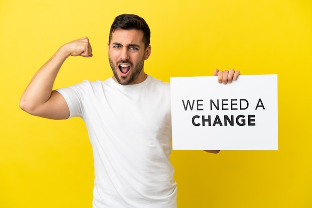 黄色の背景に分離された若いハンサムな白人男性がテキストのプラカードを保持している私たちは変更が必要であり、強いジェスチャーをしています