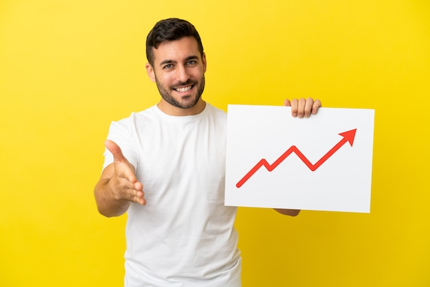 Молодой красивый кавказский мужчина изолирован на желтом фоне с табличкой с растущим символом стрелки статистики, заключая сделку