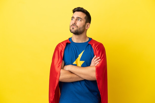 Молодой красивый кавказский мужчина изолирован на желтом фоне в костюме супергероя со скрещенными руками