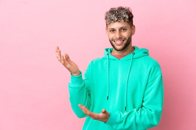 Young handsome caucasian man isolated on pink background extending hands to the side for inviting to come