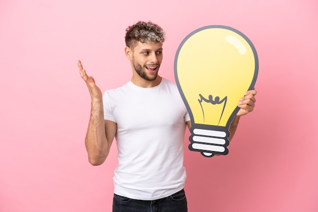 Young handsome caucasian man isolated on pink background holding a bulb icon with surprised expression