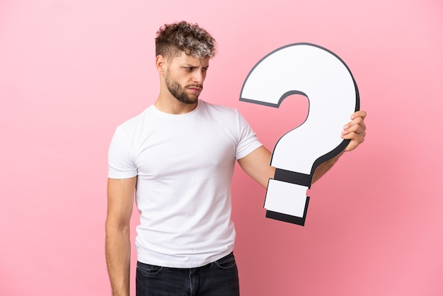 Young handsome caucasian man isolated on pink background holding a question mark icon and with sad expression