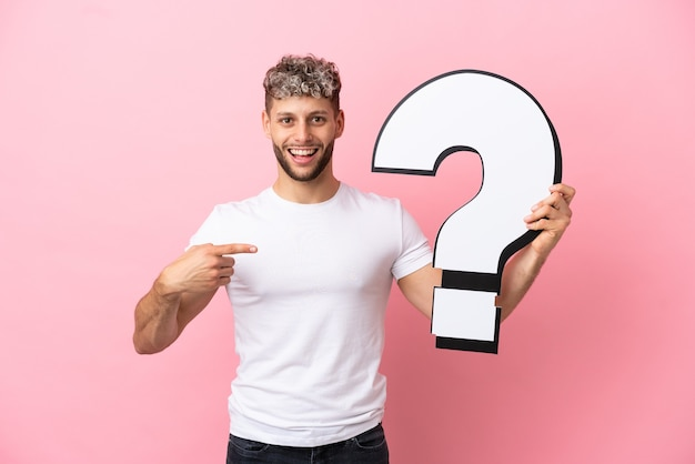 Young handsome caucasian man isolated on pink background holding a question mark icon with surprised expression