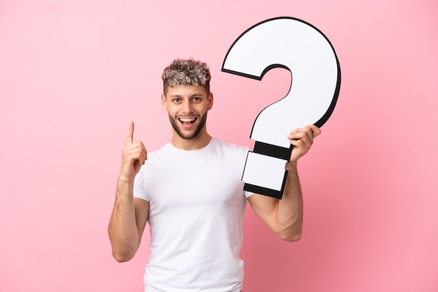 Young handsome caucasian man isolated on pink background holding a question mark icon