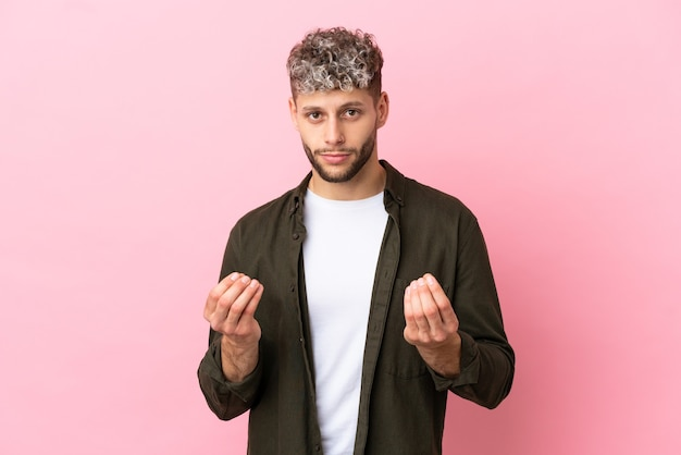 Young handsome caucasian man isolated on pink background making money gesture but is ruined