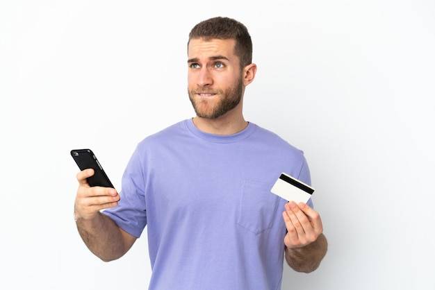 Young handsome caucasian man isolated on white wall buying with the mobile with a credit card while thinking