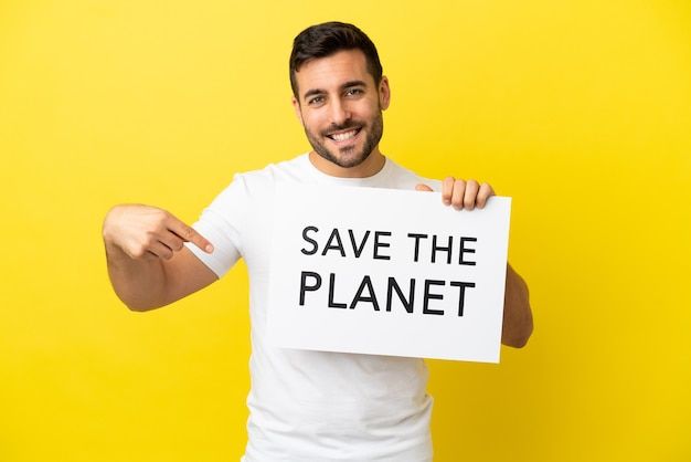 Young handsome caucasian man isolated on yellow background holding a placard with text save the planet and pointing it
