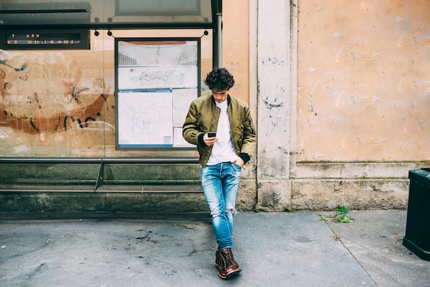 Молодой красивый кавказских человек, опираясь на автобусной остановки