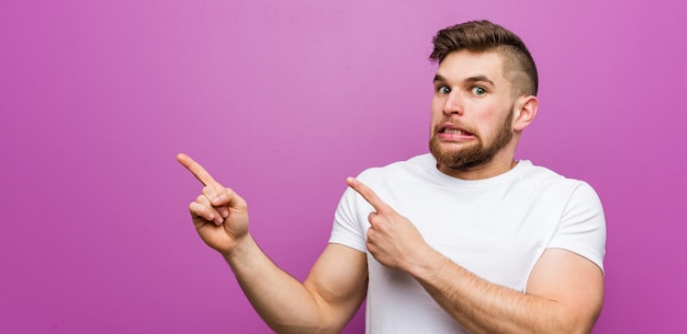 Young handsome caucasian man shocked pointing with index fingers to a blank space.