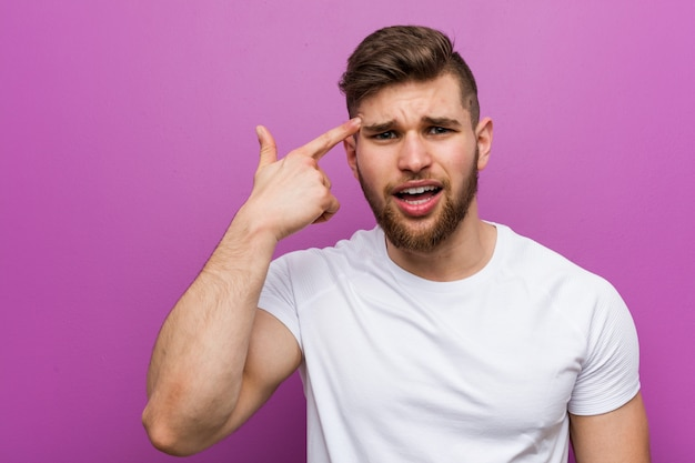 Young handsome caucasian man showing a disappointment gesture with forefinger.