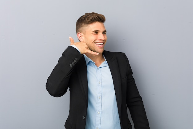 Young handsome caucasian man showing a mobile phone call gesture with fingers.