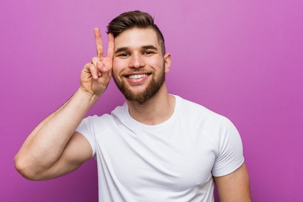 Young handsome caucasian man showing victory sign and smiling broadly