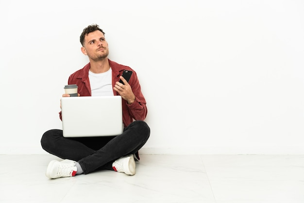 Young handsome caucasian man sit-in on the floor with laptop holding coffee
