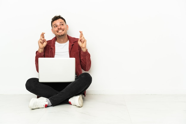 Young handsome caucasian man sit-in on the floor with laptop with fingers crossing