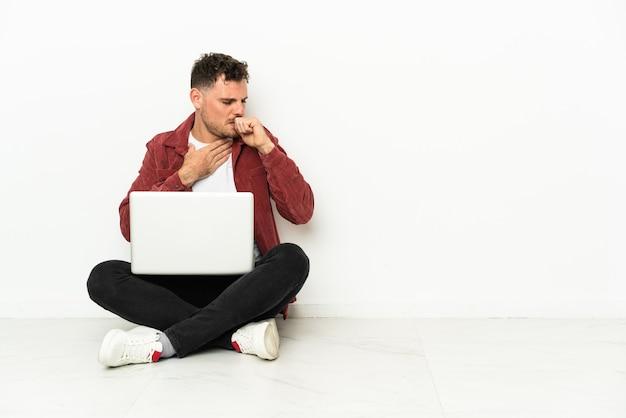 Сидячая забастовка молодого красивого кавказца на полу с ноутбуком страдает от кашля и плохо себя чувствует