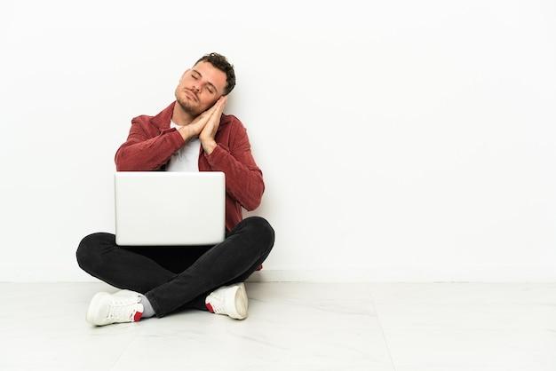 若いハンサムな白人男性が愛らしい表情で睡眠ジェスチャーをするラップトップで床に座ります