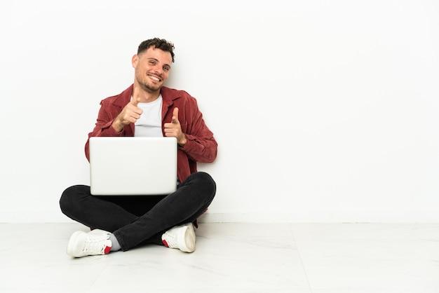 노트북이 전면을 가리키고 웃고 바닥에 앉아 젊은 잘 생긴 백인 남자