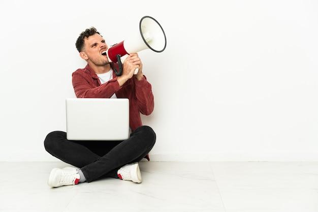 노트북은 확성기를 통해 소리와 함께 바닥에 앉아 젊은 잘 생긴 백인 남자