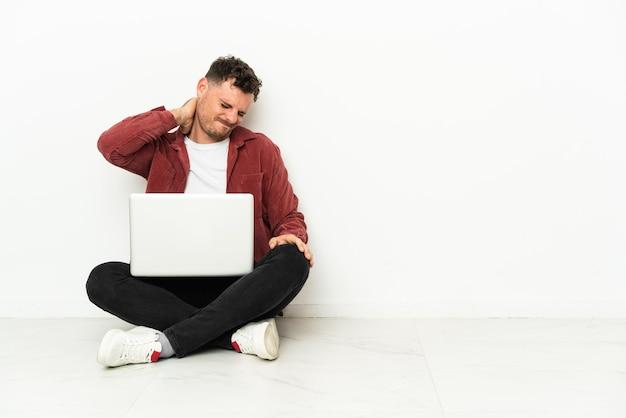 Neckache와 노트북 바닥에 앉아 젊은 잘 생긴 백인 남자