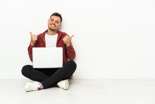 若いハンサムな白人男性が親指を立ててジェスチャーと笑顔でラップトップで床に座ります