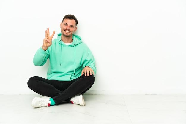 Молодой красивый кавказский мужчина сидит на полу счастливым и считает три пальцами