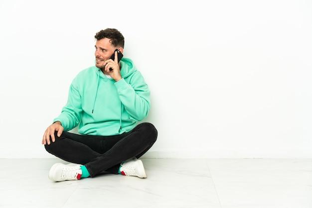 누군가와 휴대 전화로 대화를 유지하는 바닥에 앉아 젊은 잘 생긴 백인 남자