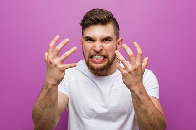 Young handsome caucasian man upset screaming with tense hands.