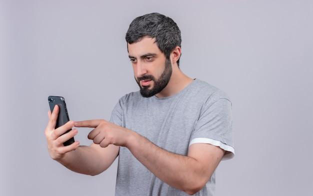 Молодой красивый кавказский мужчина с помощью своего мобильного телефона на белом фоне с копией пространства