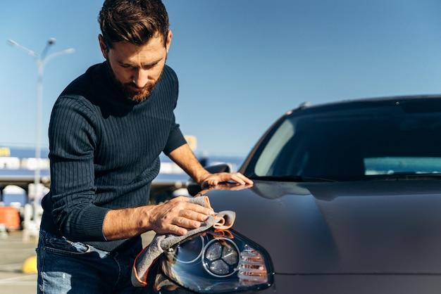 젊은 잘생긴 백인 남자는 야외에서 현대적인 검은색 차를 닦고 닦습니다. 회색 극세사를 가진 수염난 남자가 새 전기 자동차를 닦습니다. 세차 개념