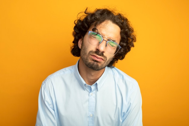 Young handsome caucasian man wearing glasses closing eyes isolated on orange background