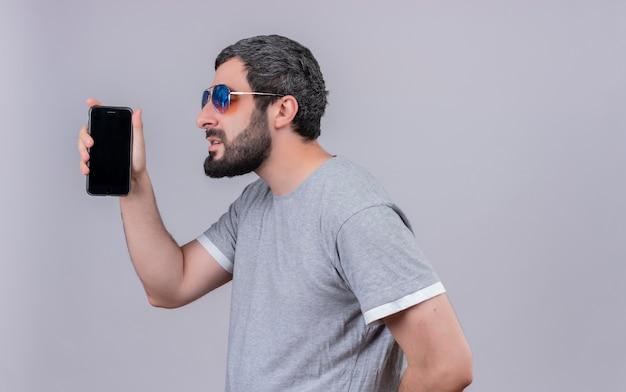 Молодой красивый кавказский мужчина в солнцезащитных очках, стоящий в профиле и держащий мобильный телефон на белом фоне с копией пространства