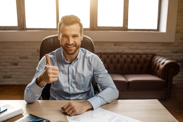 Young handsome cheerful businessman sit on table and pose in his own office. he hold big thumb up and smile. nice happy guy. sunlight.