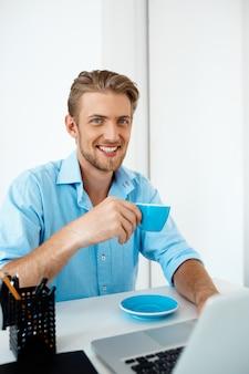 コーヒーを飲みながらラップトップに取り組んでいるテーブルに座っている若いハンサムな陽気な自信を持っているビジネスマン。笑って。白い近代的なオフィスインテリア