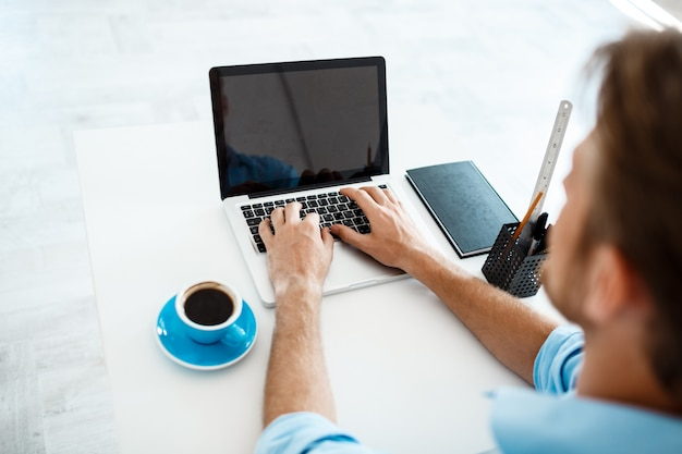 Young handsome cheerful confident pensive businessman sitting at table working on laptop with cup of coffee aside. white modern office interior