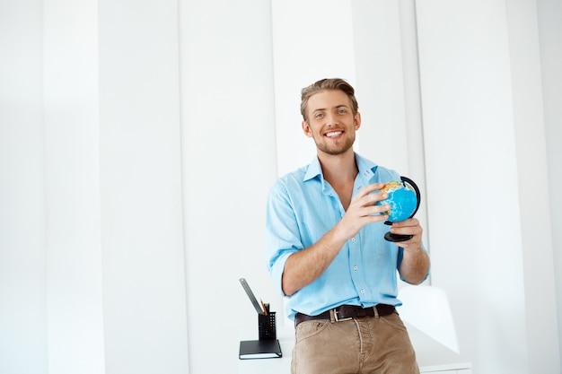 Молодой красивый жизнерадостный уверенно усмехаясь бизнесмен стоя на таблице держа малый глобус. , белый современный офисный интерьер